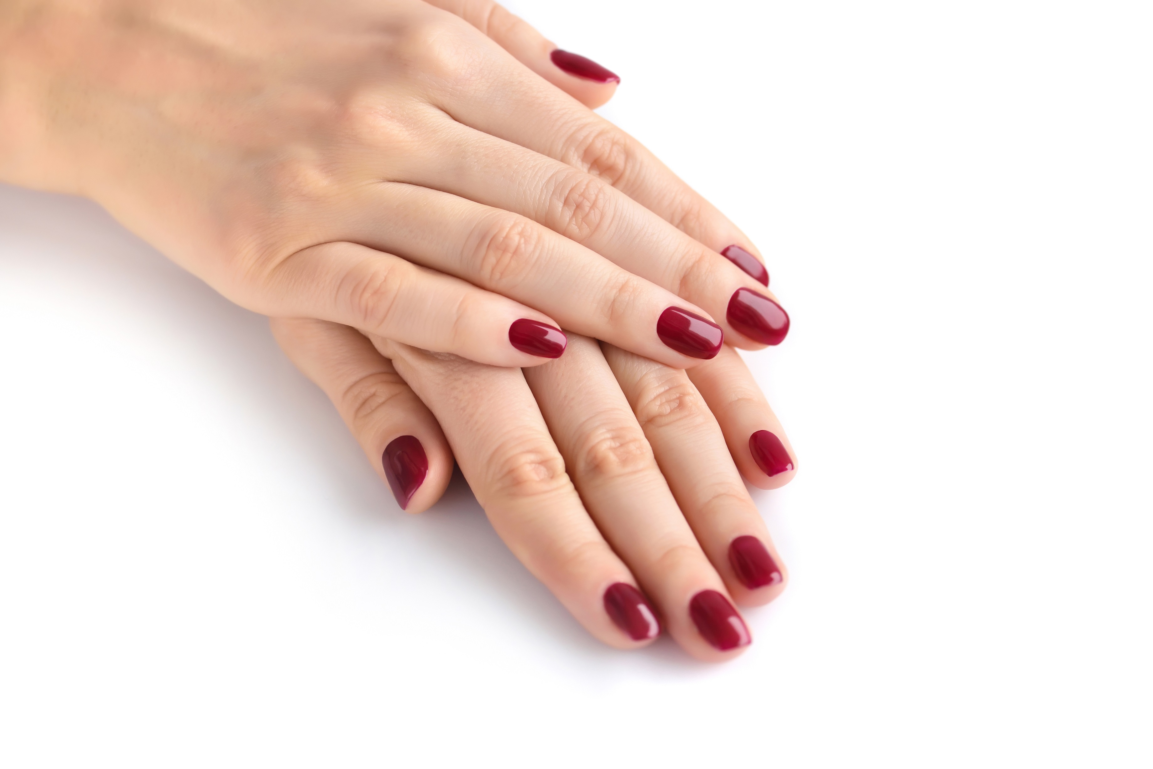 Closeup of hands of a young woman with red manicure on nails aga ...